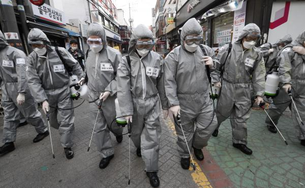 Korean soldiers spray disinfectant as a precaution against the coronavirus on a shopping street in Seoul, South Korea, last week. U.S. military stationed in South Korea and Italy have been ordered not to travel because of the outbreak.