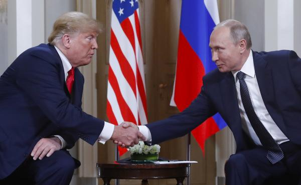 President Trump and Russian President Vladimir Putin shake hands at their summit in Helsinki, Finland, on Monday. Trump upset many in the U.S. intelligence community by refusing to endorse their finding that Russia interfered in the 2016 presidential elec