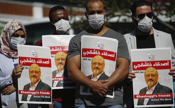 People hold posters of slain Saudi journalist Jamal Khashoggi, near Saudi Arabia's consulate in Istanbul in the fall, marking the two-year anniversary of his death.