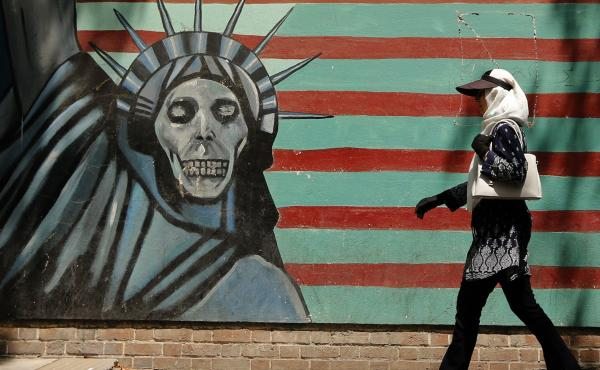 An Iranian woman walks past the former U.S. Embassy in Tehran, which bears a mural depicting the Statue of Liberty with a dead face. With just days to go until the U.S. plans to snap more sanctions back into place, questions linger about what the move spe