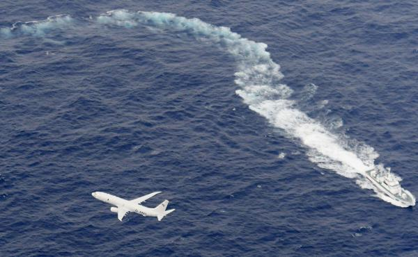 A U.S. Navy plane flies above a Japan Coast Guard patrol vessel during search-and-rescue efforts last week off the coast of Kochi prefecture, in southern Japan.