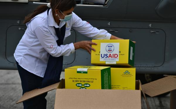 A government employee in the Honduras unpacks some of the 8,000 COVID-19 diagnostic testing kits donated by the United States Agency for International Development (USAID) and the International Organization for Migration.