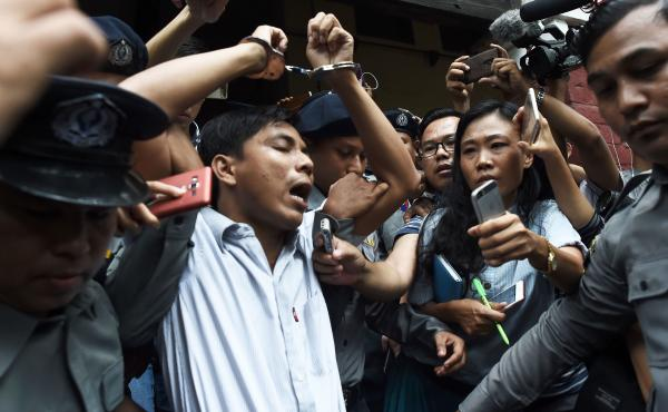 After being sentenced on Monday to seven years, Kyaw Soe Oo is escorted out of the courthouse by police. He and fellow Reuters journalist Wa Lone were accused of breaking a law on state secrets.