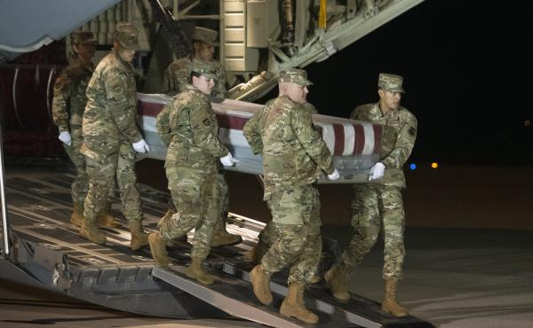 An Air Force team moves a transfer case containing the remains of one of the young sailors killed after a Saudi military student opened fire at a Pensacola naval base last month. Officials are expected to soon announce that about 20 Saudi military student