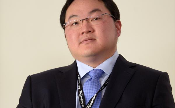 Accused of misappropriating billions of dollars, Jho Low has reached a settlement over U.S. claims related to more than $700 million in assets. But he also says he will continue to fight the charges. The Malaysian financier is seen here in 2014.