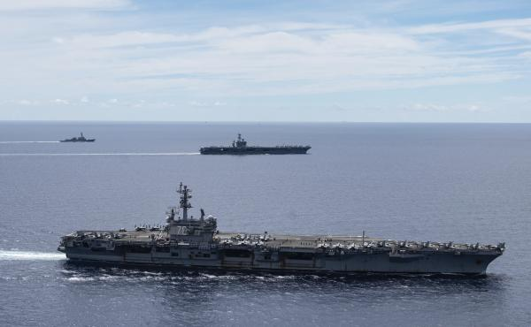 The USS Ronald Reagan (foreground) and the USS Nimitz Carrier Strike Groups sail together in formation in the South China Sea on July 6. China has accused the U.S. of flexing its military muscles by conducting joint exercises with two U.S. aircraft carrie