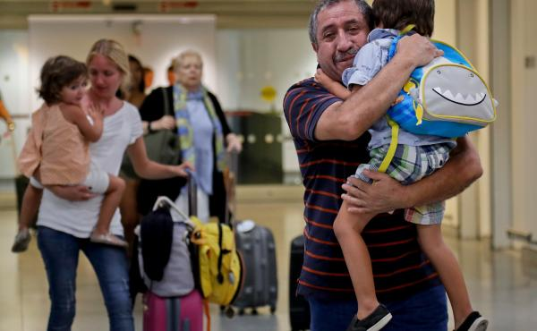 Juan Rojas (right), of Queens, N.Y., hugs his 4-year-old grandson Elias Rojas as his daughter-in-law Cori Rojas (left) carries her daughter, Lilly, 3, through the terminal at JFK airport on Tuesday after they arrived on a flight from San Juan, Puerto Rico