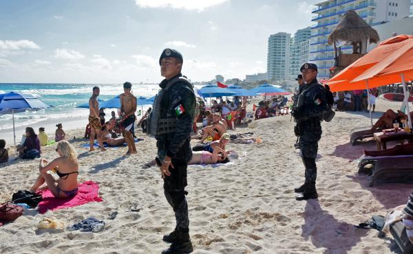 Mexican federal police patrol a beach in Cancun earlier this year, after a shooting at a local nightclub the day before.