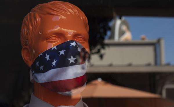 """A mannequin wears a face mask at the Citadel Outlets in Commerce, Calif. Gov. Gavin Newsom on Thursday urged Californians to turn to their """"better angels"""" and use common sense over the holiday weekend by wearing a mask and skipping traditional gatherings"""