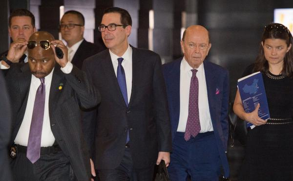 "Treasury Secretary Steven Mnuchin (center left) and Commerce Secretary Wilbur Ross (center right) walk through a hotel lobby as they head to a state guest house to meet Chinese officials in Beijing on Friday. The talks included a ""thorough exchange of vie"