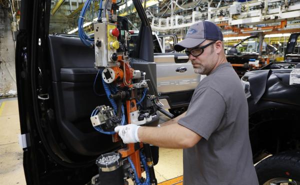 A worker installs a door on a 2018 Ford F-150 truck at an assembly plant in Dearborn, Mich., on Sept. 27. The U.S. unemployment rate fell to 3.7 percent in September, a nearly 50-year low.