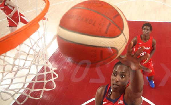 USA's Sylvia Fowles goes to the basket past Japan's Evelyn Mawuli (R) in the women's preliminary round between Japan and USA during the Tokyo 2020 Olympic Games on Friday.