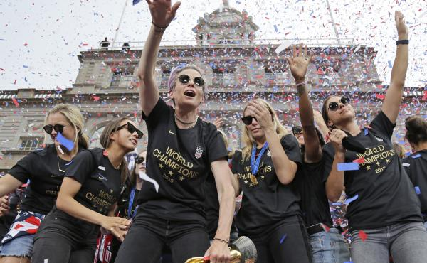 "Megan Rapinoe (center) and Alex Morgan (right), pictured celebrating with U.S. women's soccer teammates in New York after a ticker tape parade, on July 10, 2019. ""We are pleased that the USWNT Players have fought for – and achieved – long overdue equa"