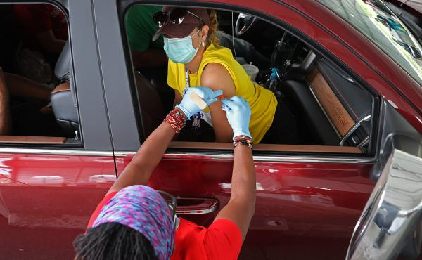 People who need help getting to a vaccination site will be able to get free or discounted rides through Uber and Lyft, the White House says. Here, a woman receives her first dose of the Pfizer vaccine at a mass vaccination site in Aberdeen, Md., after get