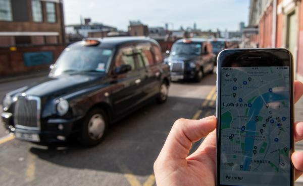 A phone shows the Uber app in front of a taxi stand at Waterloo station in London on Monday. The ride-sharing service won its appeal after Transport for London denied a renewal of its operating license late last year.