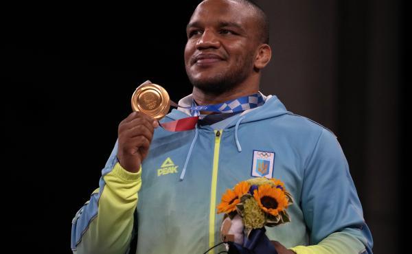 Gold medalist Zhan Beleniuk of Ukraine celebrates on the podium during the medal ceremony for men's 87-kilogram Greco-Roman wrestling.