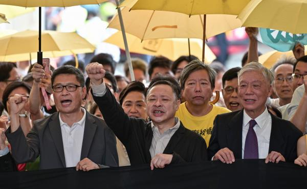 Sociology professor Chan Kin-man (left), law professor Benny Tai (center), and Baptist minister Chu Yiu-ming (right) chant slogans before entering the West Kowloon Magistrates Court in Hong Kong on Wednesday to receive their sentences after being convicte
