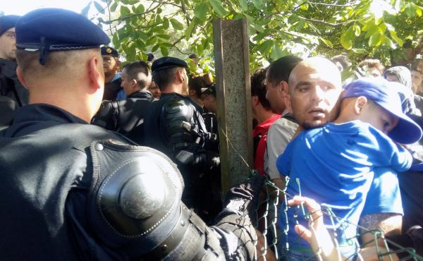 Croatian police in riot gear stand guard over migrants and refugees on the Serbia-Croatia border.