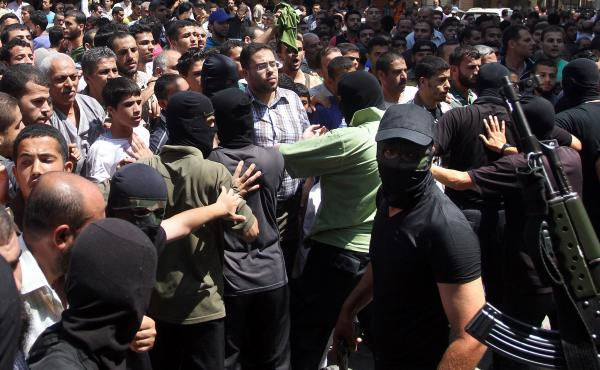 Armed Palestinian masked militants push back a crowd of worshippers outside a mosque in Gaza City on August 22, 2014, before executing more than a dozen men for allegedly helping Israel during its six-week assault on the Palestinian enclave. This week, Am
