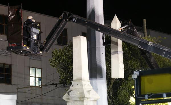 Workers dismantle the Battle of Liberty Place monument on Monday in New Orleans.