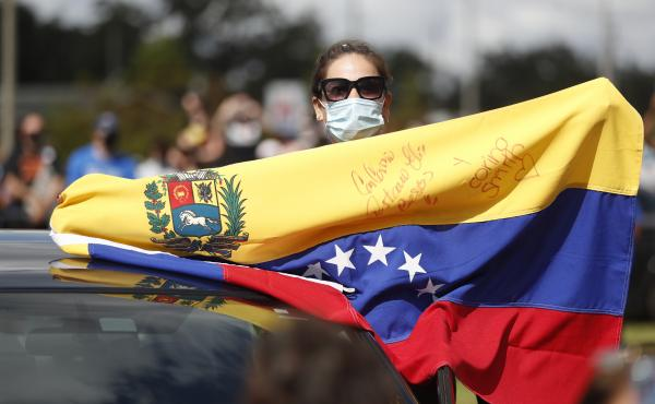 A Joe Biden supporter with a Venezuelan flag cheers during a Biden campaign event at Camping World Stadium on October 27, 2020 in Orlando, Florida.