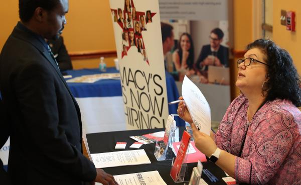 Betty Fernandez of Macy's department store speaks with a potential applicant about job openings during a job fair in Miami on April 5. Employers added far more jobs than expected in April — another sign the U.S. economy is chugging along as the expansio