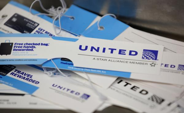 United Airlines baggage tags are displayed on a table at San Francisco International Airport. The carrier says it's starting a pilot program next month that will offer rapid coronavirus testing at the airport or via a self-collected, mail-in test ahead of