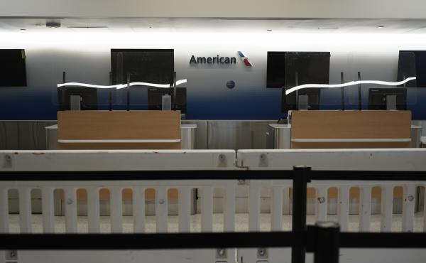 American Airlines check-in counters sit closed last month behind plastic barriers at Los Angeles International Airport.
