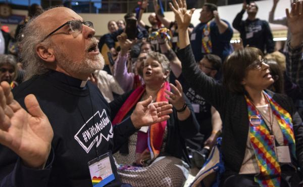 Protesters sing and pray outside the United Methodist Church's special session of the general conference in St. Louis on Tuesday. Delegates voted to maintain current rules against gay clergy and same-sex marriage.