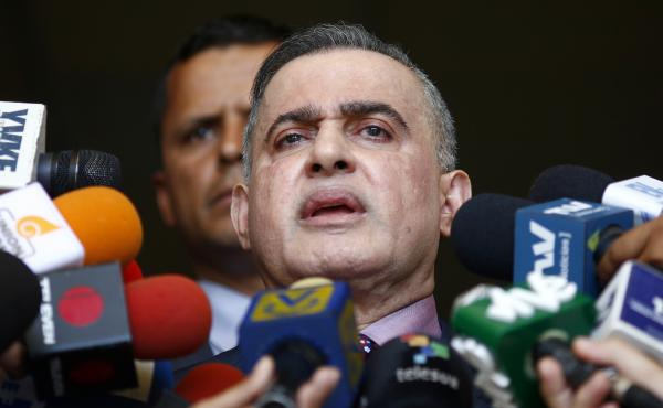 Venezuela's top prosecutor, Tarek William Saab, talks to reporters in Caracas on Tuesday. He announced that Juan Guaidó, now President Nicolás Maduro's most prominent opponent, is barred from leaving the country because of an investigation.