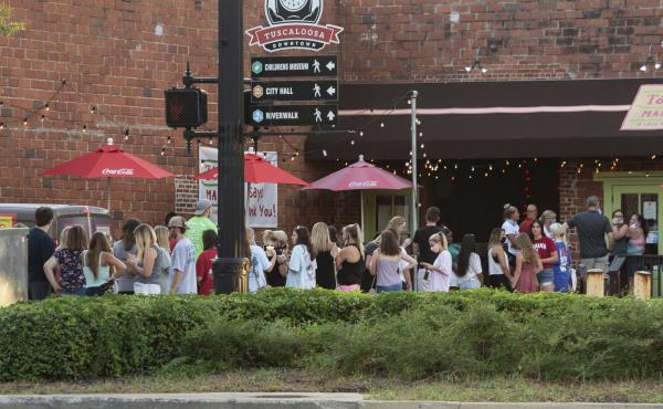 People line up outside to order food from a taco restaurant in Tuscaloosa, Ala. Social media images of crowds outside bars drew scrutiny last weekend in the city, which is home to the University of Alabama.