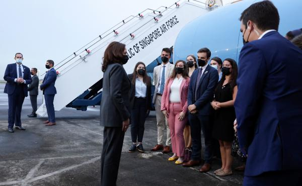 Vice President Harris (center) speaks with U.S. personnel as she departs Tuesday from Singapore on her way to Vietnam.