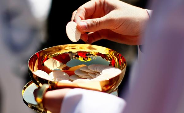A priest holds a Holy Communion wafer in Washington, D.C.