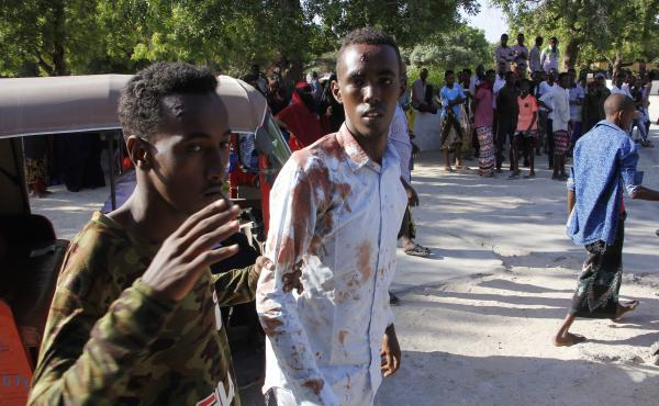A civilian who was wounded in suicide car bomb attack is helped by a friend at checkpoint in Mogadishu, Somalia, Saturday.
