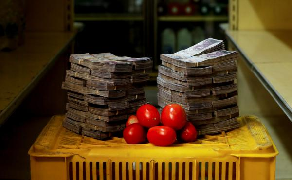 """A kilogram, or just over 2 pounds, of tomatoes sits next to the 5 million """"strong"""" bolivars needed to buy the bunch at an informal market in a low-income neighborhood of Venezuela's capital, Caracas."""
