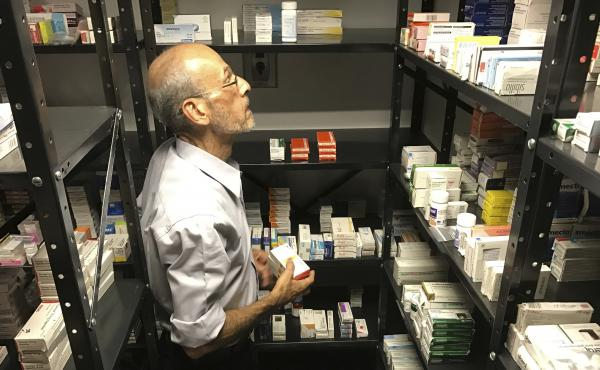 A volunteer from the non-profit Accion Solidaria organizes imported medicines alphabetically, in a store room in Caracas, Venezuela, last April. The Pharmaceutical Federation of Venezuela estimates the country is suffering from an 85 percent shortage of m
