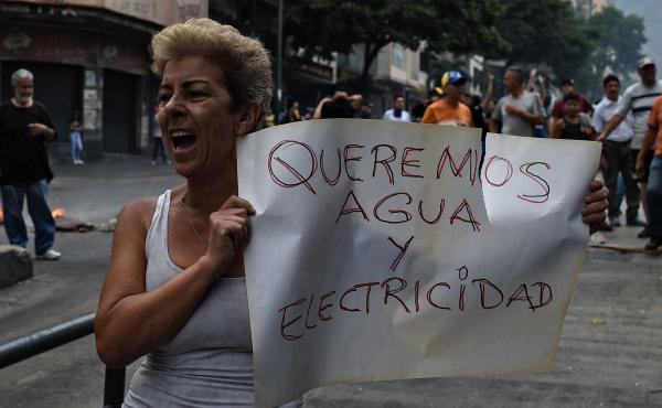 """A woman holds a placard reading """"We Want Water and Electricity"""" as she shouts slogans during a protest in Caracas, Venezuela, about a lack of water and electric service during a new power outage in the country on Sunday. President Nicolás Maduro announce"""