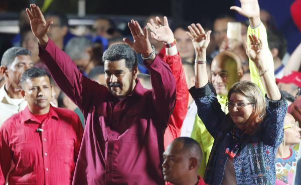 Venezuela's President Nicolás Maduro and his wife, Cilia Flores, wave to supporters at the presidential palace in Caracas on Sunday after election officials declared his victory.