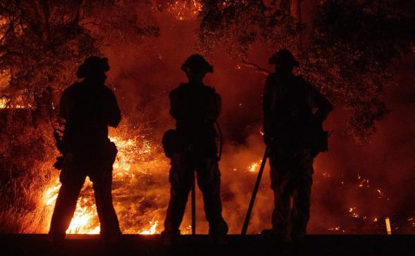 Firefighters keep watch on an area of the Mendocino Complex Fire in Upper Lake, Calif.