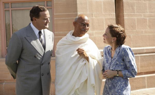 Lord Louis Mountbatten (Hugh Bonneville), Mahatma Gandhi (Neeraj Kabi) and Lady Edwina Mountbatten (Gillian Anderson) smile politely in The Viceroy's House.