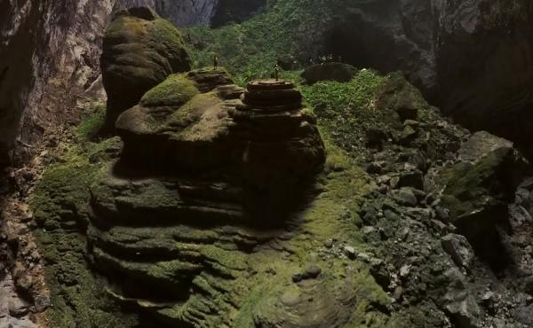 Yes, those are people: A still image from a drone video filmed inside the world's largest cave shows cavers standing beneath one of two large skylights in Vietnam's Hang Son Doong.