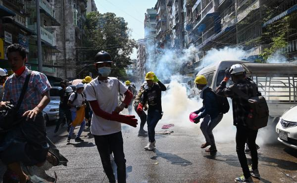 Protesters in Yangon run from police Sunday after they fire tear gas during a demonstration against the military coup.
