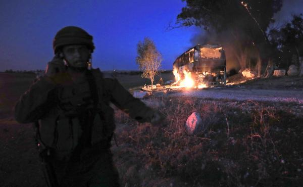 An Israeli soldier stands near a burning bus that was hit by a mortar shell fired from Gaza on Monday.