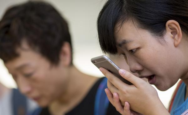 A customer tries the Siri voice recognition function on an Apple iPhone 6 Plus in Hong Kong.