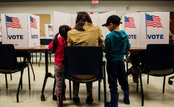 A woman and her children vote at a polling station during the mid-term elections at the Fairfax County bus garage in Lorton, Va.