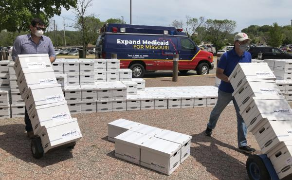 Campaign workers David Woodruff, left, and Jason White, right, deliver boxes of Medicaid expansion initiative signatures to the Missouri secretary of state's office in Jefferson City, Mo. on May 1, 2020.