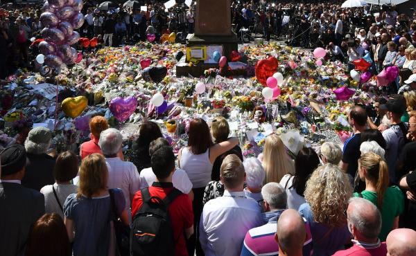 People stop to observe a minute's silence in St. Ann's Square in central Manchester,  England, on Thursday to remember victims of Monday's bombing.