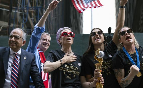 From left, U.S. Soccer Federation President Carlos Cordeiro, New York Mayor Bill de Blasio and soccer players Megan Rapinoe, Alex Morgan and Ashlyn Harris celebrate the U.S. women's soccer team's world championship in New York, during a ticker tape parade
