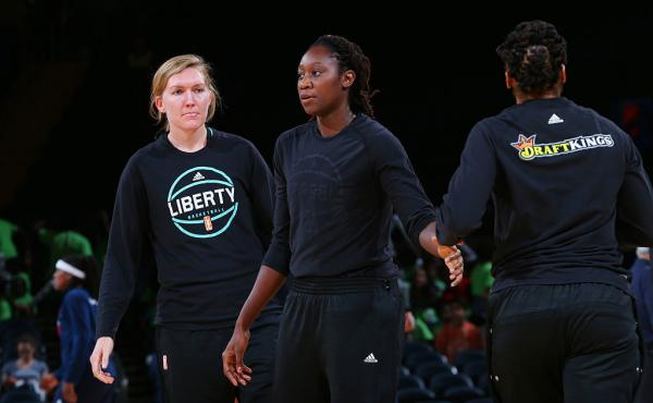 Carolyn Swords (left) and Tina Charles (right) of the New York Liberty look on before the game against the Indiana Fever on Thursday at Madison Square Garden in New York, New York. Charles says she turned her warmup shirt inside out in support of recent s