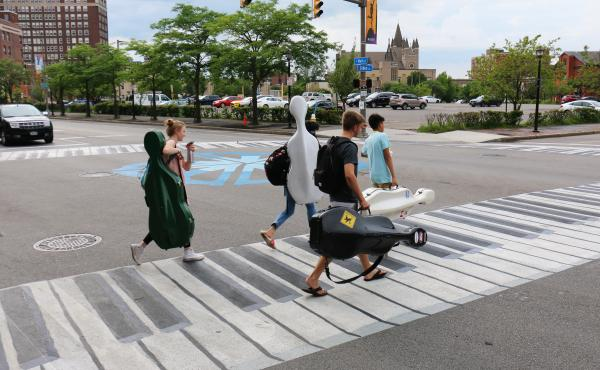Musicians walk on a crosswalk painted like a piano outside the Eastman School of Music in Rochester, N.Y. Increasingly, urban designers and transportation planners say this kind of art — colorful crosswalks and engaging sidewalks — leads to safer inte